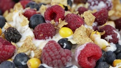 Cereal flakes with blueberry , raspberry , sea buckthorn. Muesli food background Stock Footage