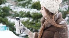 Pretty girl pouring hot tea from thermos into a cup. Slowly Stock Footage