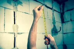 Worker with tape measure in centimeters and feets Stock Photos