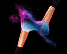 Makeup brush with blue powder explosion on black Stock Photos