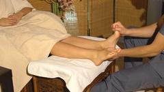 Beautiful blonde girl doing foot massage. Therapeutic massage Stock Footage