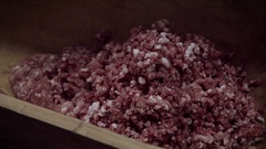 Making of hungarian pork sausage, milling raw meat into trough Stock Footage