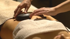 Massage with hot basalt stones Stock Footage