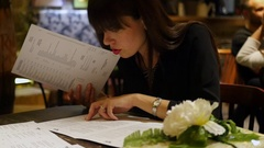 Beautiful girl chooses the menu looks Stock Footage
