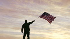 4K. Soldier silhouette waves American Flag, sunrise time   Stock Footage