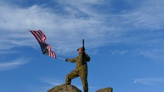 4K. Soldier silhouette with rifle waves American Flag against blue sky Stock Footage