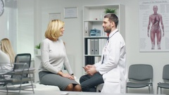 Male Doctor Consults His Mid Adult Female Patient. Nurse Busily Works  Stock Footage