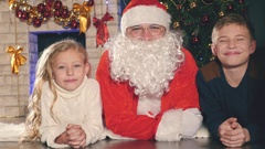 Santa and kids near the decorated Christmas tree. Wishes list Stock Footage