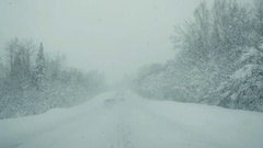 Car driving on snow road during strong snowfall in slowmotion. 1920x1080 Stock Footage