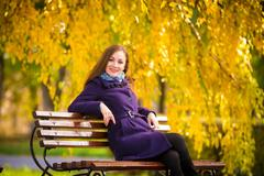 Young girl sitting on the bench warm autumn day Stock Photos