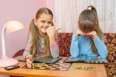 Older sister hurt her younger sister and laughing at her Stock Photos