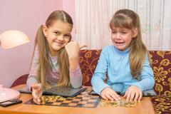 Two girls at the table collected montki one cries, the other laughs at it Kuvituskuvat