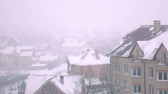 Super slow motion shot of snowstorm above sloped roofs of residential houses in Stock Footage