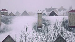 Super slow motion pan shot of snowstorm above sloped roofs of residential houses Stock Footage
