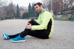 Runner with injured ankle while training in the city park in cold weather Stock Photos