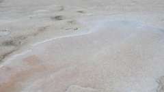 Camera tilt up from crystal salt rock salty beach shore to red pink sea water Stock Footage