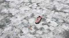 A shoe on crystal salty beach shore with red pink sea water and a rock hill Stock Footage