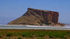 Pan over a rock hill near crystal salt rock salty beach shore of a red pink sea Stock Footage