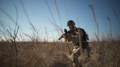 Airsoft soldier with a rifle and full NATO ammunition aiming in the field Stock Footage