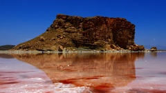 Tilt down high rock hill near red pink sea water to crystal salty beach shore Stock Footage