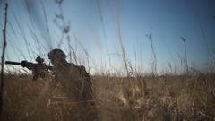 Airsoft soldier with a rifle and full NATO ammunition squats down in the field Stock Footage
