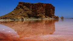 Pan from rock hill near red pink sea water to salt crystal salty beach shore Stock Footage