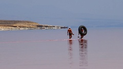 Two men going to swim in a red pink sea with a tube in a surrealistic atmosphere Stock Footage