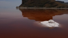 Crystal salt rock inside the red pink sea water with mountains in the background Stock Footage