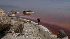 Tourist taking picture from crystal salt rock inside the red pink sea water Stock Footage