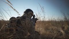 Airsoft soldier squats down and aims with a rifle and full NATO ammunition Stock Footage