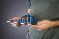 Businessman analyzing financial statistics displayed on the tablet screen. Stock Photos