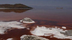 Pan on a salty beach shore with red pink water and mountains in the background Stock Footage