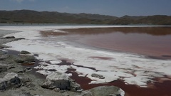 Pan over a salty beach shore with red pink water and mountains in the background Stock Footage