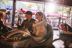 Friends on bumper car ride in amusement park Kuvituskuvat