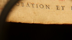 4K old book is seen through a magnifying glass Stock Footage