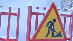 Traffic barriers and road signs at steaming heat pipeline damage in the winter Stock Footage