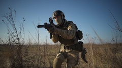 Soldier in full NATO ammunition walks in field, squats down, aims with a rifle Stock Footage