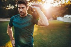 Fit young man exercising with kettlebell in park Stock Photos