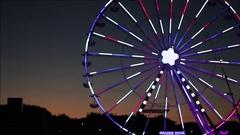 Ferris wheel with multi colored illumination against the dark blue night sky  HD Stock Footage