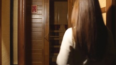 Young woman relaxing in a sauna. Gorgeous girl sitting in sauna Stock Footage