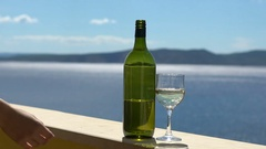 Best vacation, young girl is drinking wine on the balcony of house near the sea Stock Footage