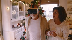 Senior couple in front of Christmas tree. Man with VR goggles Stock Footage