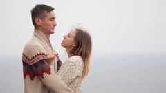 Young attractive couple in knitted sweaters on a cliff on sea shore Stock Footage