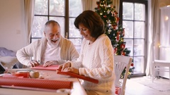 Senior couple in sweaters wrapping Christmas gifts together Stock Footage