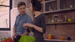 Attractive girl and handsome guy cook and talk in apartment Stock Footage