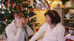 Senior couple in front of Christmas tree wearing deer antlers Stock Footage
