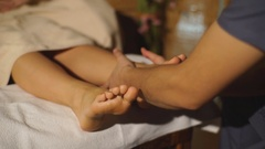 Beautiful caucasian blonde do a foot massage Stock Footage