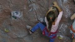 Rock climbing. Little girl climbing on training wall in climbing center Stock Footage