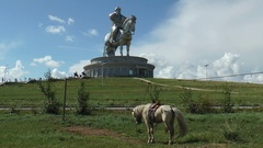 Grazing horse on the background of a huge monument to Genghis Khan. Stock Footage