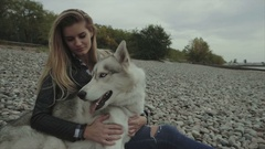 Young beautful girl with siberian husky dog sitting on the river bank Stock Footage